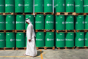 A visitor passes ENOC-branded oil barrels stored at the Emirates National Oil Co. lubricants and grease manufacturing plant in Fujairah, United Arab Emirates, on Monday, March 12, 2012. ENOC, as Dubai's government-owned refiner is known, will expand the plant's capacity to 250,000 tons a year by 2014, it said. Photographer: Gabriela Maj/Bloomberg