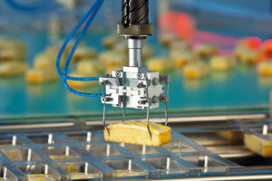 محصولات کیک و شیرینی بهآرامی با گیرههای خاصی بستهبندی میشوند. عکس: