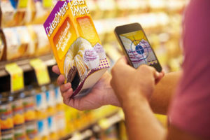 Man Scanning Voucher Code In Supermarket With Mobile Phone